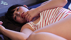 Lying On Bed Hand Rasied To Her Face Wearing Striped Top