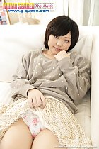 Mei Kadowaki leaning back on couch hand raised to her face cute short hair pulling her short skirt up over her panties