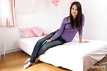 Sitting on bed long hair purple sweater in jeans hand resting on thigh bare feet