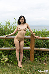 Standing Naked Beside Fence Outdoors Ocean In Background Bare Breasts Trimmed Busy Bare Feet On Grass