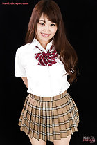 Student in uniform arms behind her back long hair plaid skirt