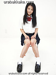 Kogal Seated On Chair In Uniform Long Hair Down To Her Chest Hands On Her Thighs Knees Pressed Together