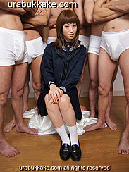 Seated In Front Of Semi Naked Men Wearing Kogal Uniform Hands Clasped Together On Her Knees