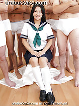 Seated in front of half naked men wearing kogal uniform hands resting on her lap
