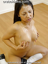 Bukkake cum running down her face and onto her breasts cupping her breasts in her hands