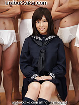 Kogal seated in uniform surrounded by semi naked men her hands resting on her lap
